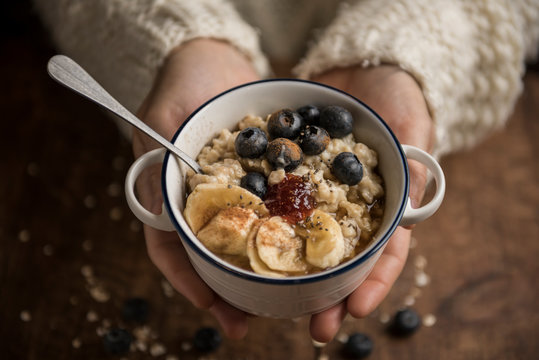 Woman hands offering a vegan porridge with oat flakes, banana, blueberries, chia, cinnamon, maple syrup and strawberry jam. Horizontal. Top view.