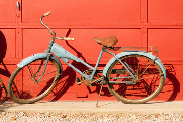 Printed kitchen splashbacks Bicycle Old antique rust bicycle in front of red garage doors in bright sunlight