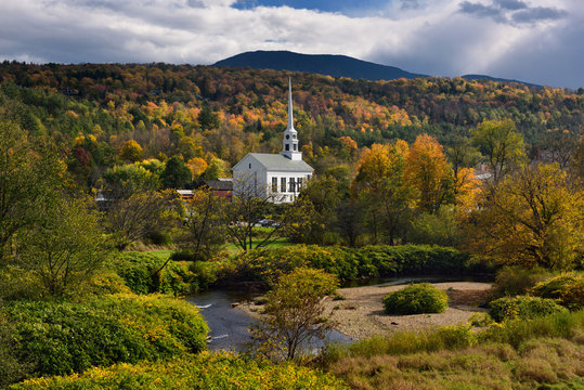Waterbury river with Stowe Community Church against Fall color on Brush Hill in Vermont