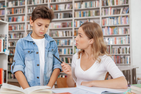 Angry mother scolding her son at the library. Annoyed mom blaming her child for bad behavour or marks at school