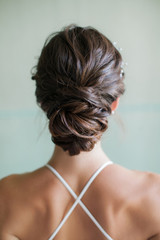 A young bride shows off her elegant dress and hairstyle from the back.
