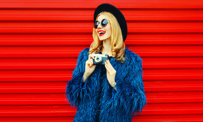 Stylish surprised woman with retro camera wearing blue faux fur coat, black round hat and sunglasses looking away over colorful red wall background