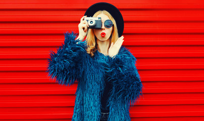 Portrait cool surprised woman with retro camera taking picture wearing blue faux fur coat, round hat and sunglasses over colorful red wall background