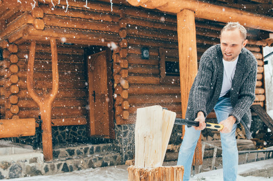Man chopping wood on snowy yard for fireplace. Winter countryside holidays concept image