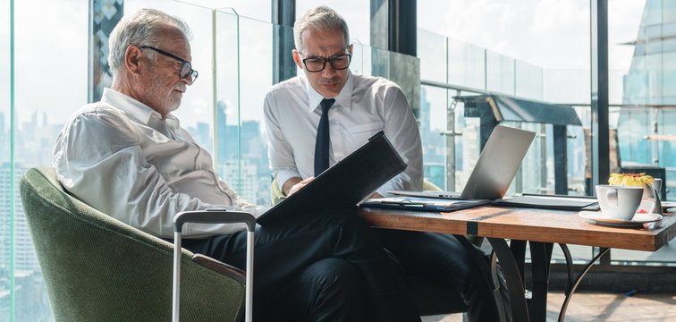 business background of senior business executive having business conversation with lawyer with laptop on table in office