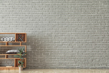 Wooden shelving unit with plant in pot and decor near brick wall