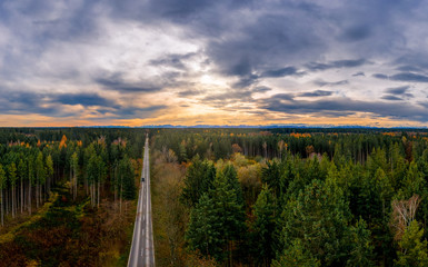 Aerial view of road among the forest and trees. Sunset field in southern germany near the alps.