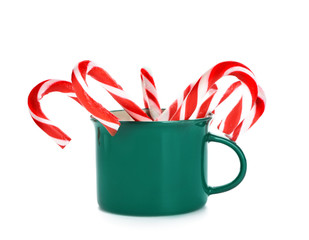 Mug with Christmas candy canes on white background
