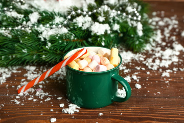Mug of hot chocolate with Christmas candy canes, marshmallows ad snow on table