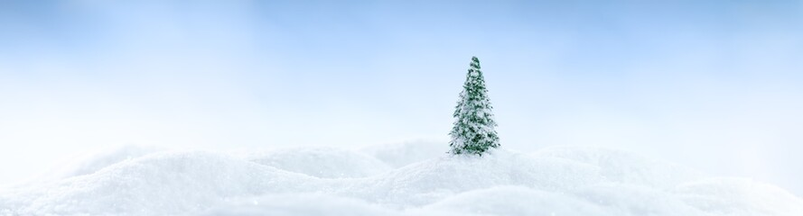 Wintery landscape background with single tree on glistening white snow drifts