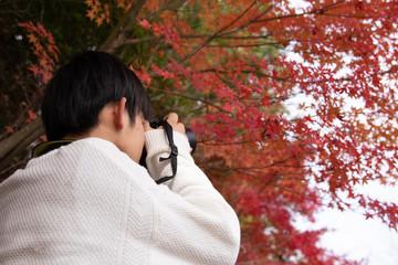 紅葉を撮影する男子高校生