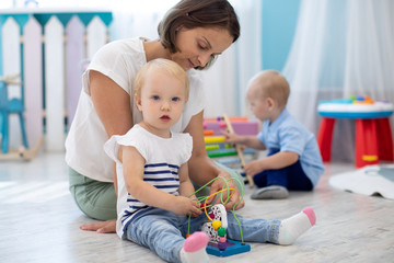 Child toddler playing with toys with teacher or babysitter indoors