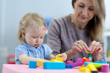 Mom and child toddler playing with developmental toys. Early education concept.
