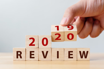 2020 review concept. Hand flip wood cube change year 2019 to 2020 and the word REVIEW on wooden...