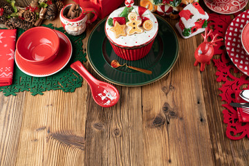 Christmas time. Christmas tableware and decorations. Red and brown colors. Rustic wooden background.