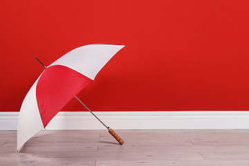 Wall Mural - Beautiful colorful umbrella near red wall. Space for text