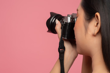 Closeup woman holding camera on pink background. Photographer working in studio. Free from copy space.