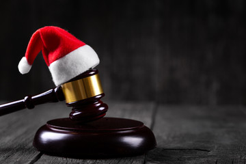Santa Claus hat on Judge Gavel on wooden rustic background
