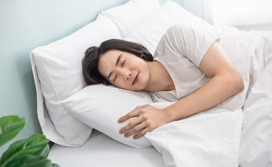 Portrait of handsome young asian man with enjoy fresh soft bedding linen mattress in white bed room modern retro apartment. Asian guy sleep resting, good night sleep concept panoramic banner