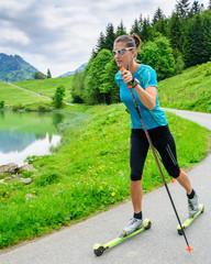 Junge Sportlerin beim Skiroller-Training im Gebirge