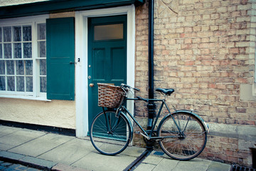 Aluminium Prints Bicycle Bicycle with a basket is leaning against the front door