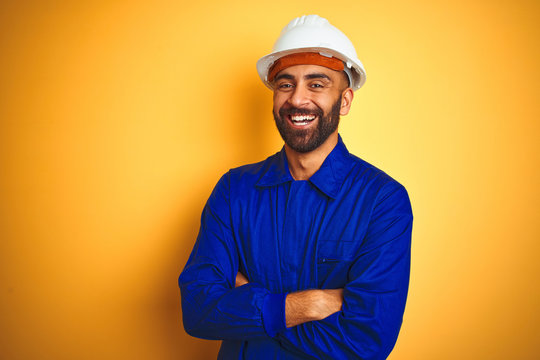 Handsome indian worker man wearing uniform and helmet over isolated yellow background happy face smiling with crossed arms looking at the camera. Positive person.