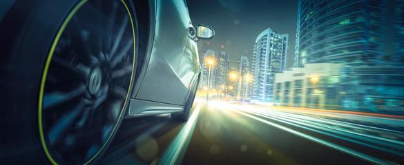 Sportwagen fährt bei Nacht in beleuchteteter Stadt Fototapete
