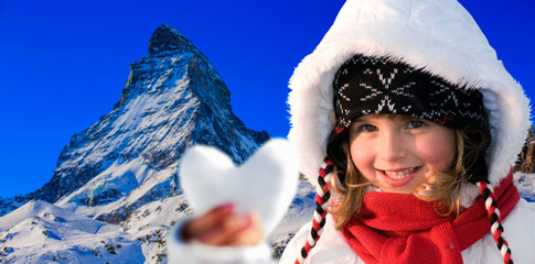 Wall Mural - Portrait of happy young girl in the snow, ski slope and Matterhorn in the background.