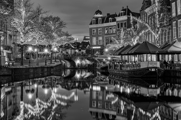 View on the New Rhine and Visbrug with terrace boats and trees with christmas ornaments during blue hour, Leiden, the Netherlands