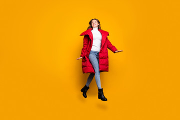 Full body profile photo of charming lady jumping high walking street amazing sunny fall day wear jeans shoes white pullover red long winter coat isolated yellow color background