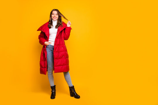 Full length photo of pretty lady traveler walking down street playing with curl wear jeans leather shoes white pullover red long winter coat isolated yellow color background