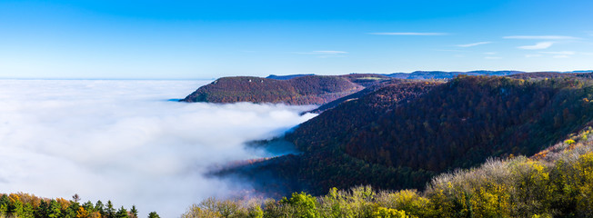 Germany, XXL panorama of beautiful aerial view above endless fog clouds in valley of swabian alb nature landscape on sunny day with blue sky near stuttgart