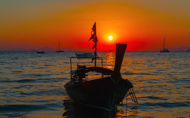 Long tail boat summer golden sunset waves reflection of sun on the beach.