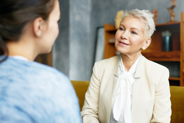 Psychology, consulting and coaching concept. Stylish middle aged female psychologist having conversation with brunette woman client, discussing problems and progress, sitting in her cozy office