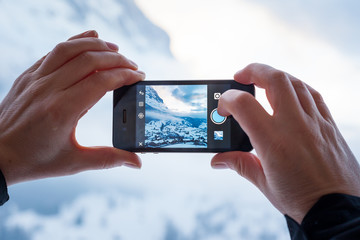 GRINDELWALD, SWITZERLAND - FEBRUARY 4, 2014: Woman taking a photograph of mountains using the Instagram App on an Apple iPhone.