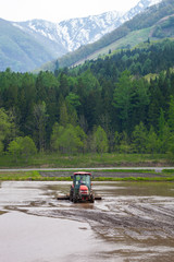 Hakuba, Japan - May 17, 2012: A flooded rice paddy field at the foot of the Hakuba mountain range being prepared for planting by a man in a tractor.