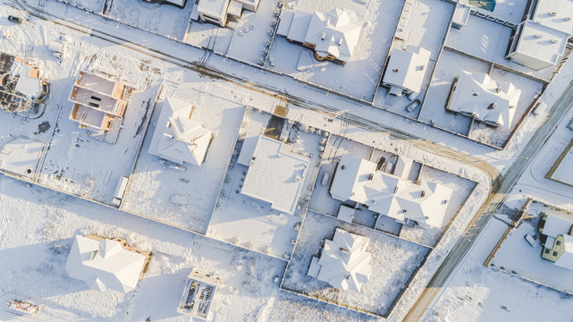 Top view of the winter village with snow covered houses and roads. Aerial view of landscape