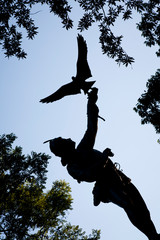 """New York City, USA - SEP 19, 2009 : Silhouette of """"The Falconer"""" statue and surrounding trees in Central Park, New York City."""