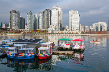 VANCOUVER, CANADA - OCTOBER 23, 2006 : Aquabus ferries moored at Granville Island with Downtown Vancouver in the background. The ferry transports commuters and tourists to destinations in False Creek.