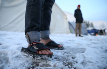 A migrant stands in a snow covered makeshift forest camp near Croatian border in Bihac