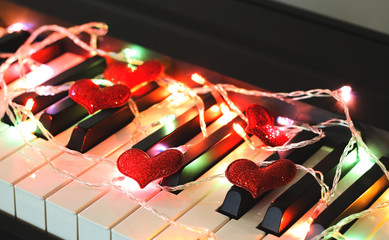 Red glitter hearts  and glowing and colorful string lights on piano .