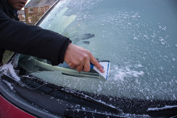 Person using a scrapper to scrape off icy and frost from the window of a red car.