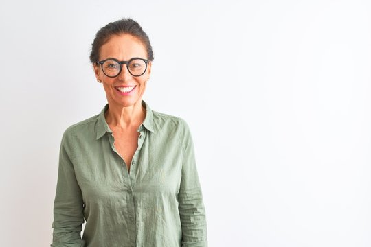 Middle age woman wearing green shirt and glasses standing over isolated white background with a happy and cool smile on face. Lucky person.
