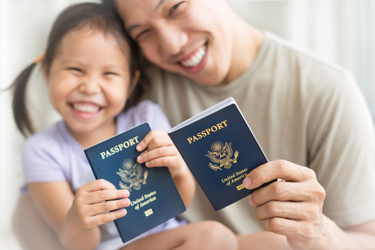 Happy immigrant family becoming new American citizens, holding US passports.