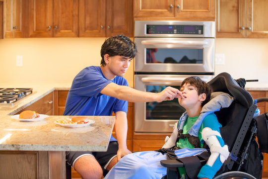Disabled boy in wheelchair in kitchen with older brother