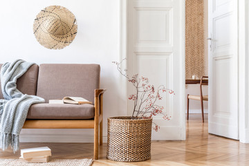 Stylish and cozy interior of living room with design brown sofa and elegant rattan accessories. Korean beige style of home decor. Minimalistic concept of interior design. Template.