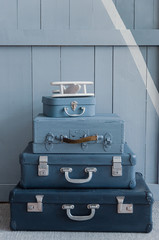 Stacked suitcases ready for the trip. Beautiful blue suitcases in the old style. Suitcase mood. Good postcard for the traveler.