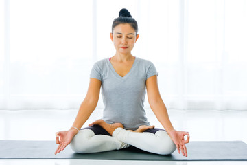 Asian woman sitting on lotus position on floor legs crossed with eyes closed for meditating in room. Yoga at home.