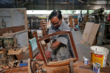 A man, who has lost his left forearm in an accident, makes a wooden chair inside a training centre for disabled people on the occasion of International Day of Disabled Persons, in Ahmedabad