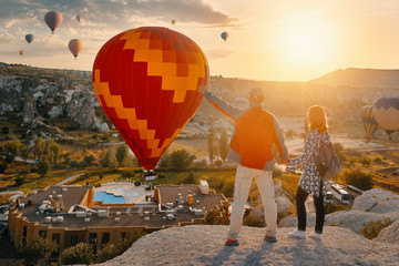 Wall Mural - Couple travelers watches colorful balloons flying on an early sunny morning in Cappadocia.Turkey.